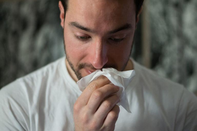 Ein junger Mann hält ein Taschentuch in der Hand. Es scheint als trockne er sich gleich eine Freudenträne.