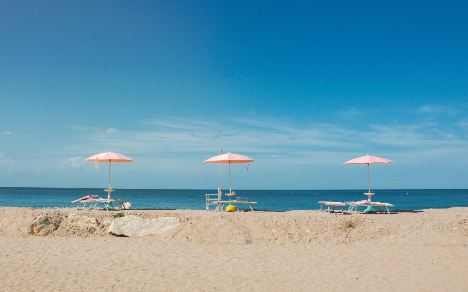 Sandstrand, Meer, blauer Himmel und Sonnenschirme